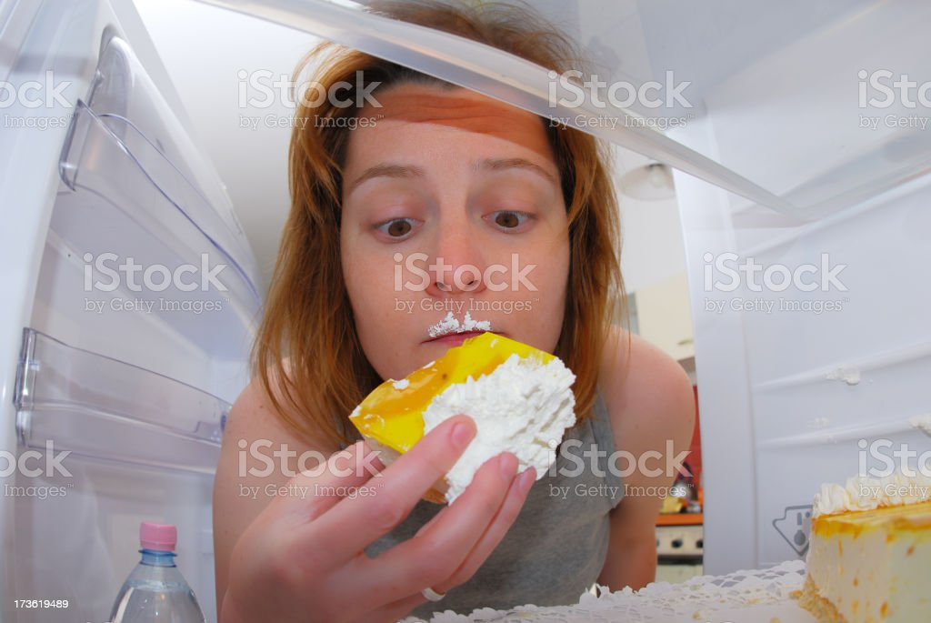 Young woman eating cake in the fridge stock photo
