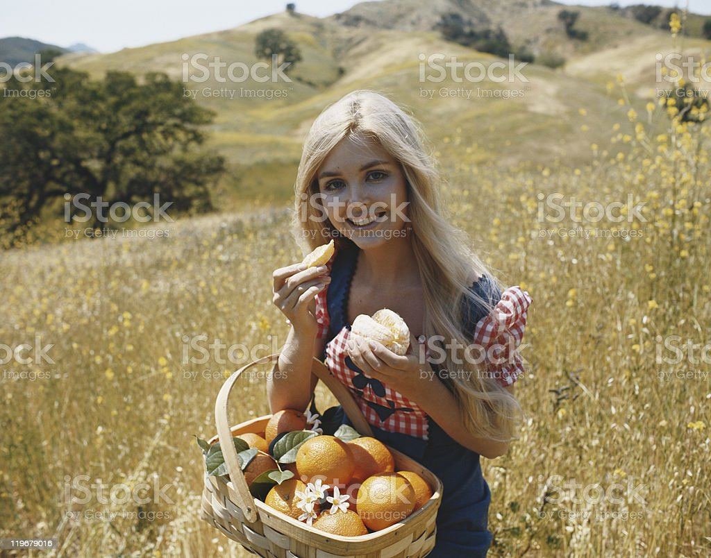 Young woman eating orange in meadow, close-up, portrait stock photo