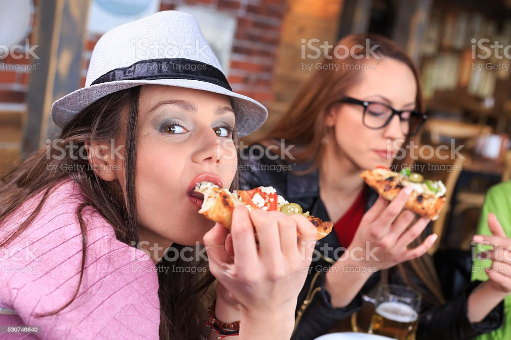 Young woman eating pizza with friends at restaurant stock photo