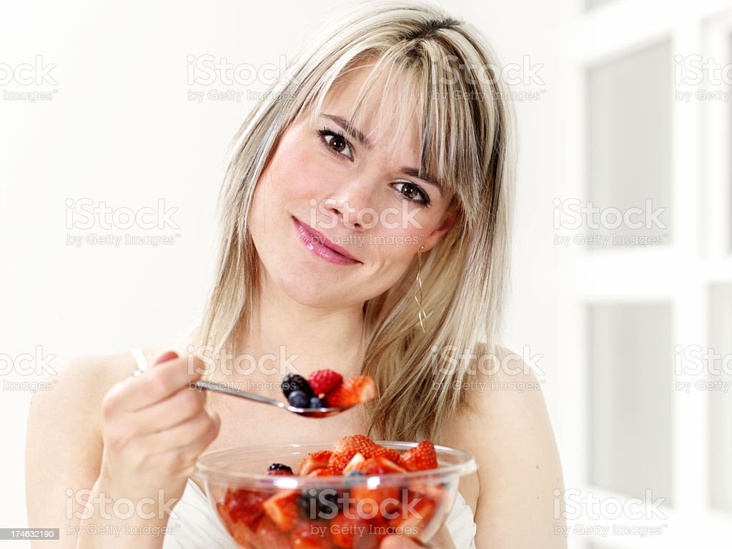 Young woman eating strawberries royalty-free stock photo