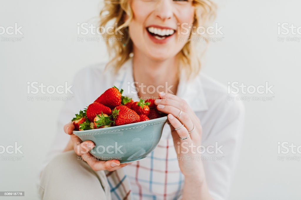 Young woman eating strawberries stock photo
