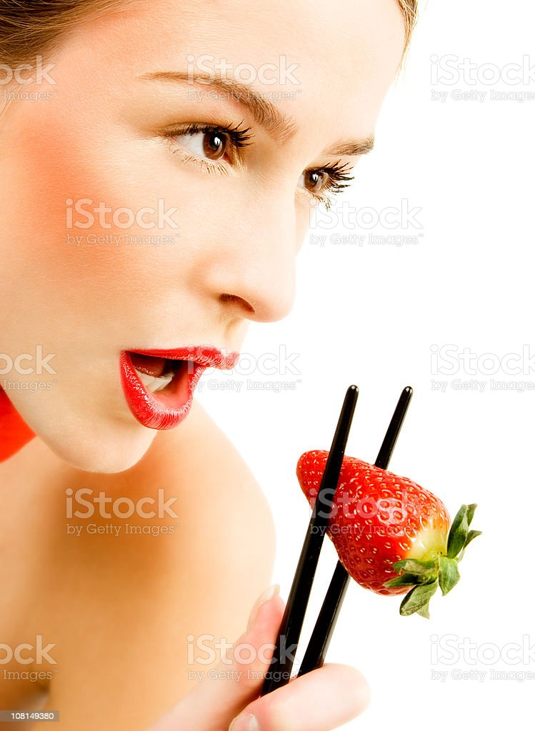 Young Woman Eating Strawberry with Chopsticks royalty-free stock photo