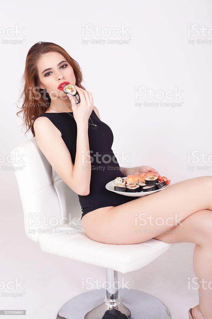Young woman eating sushi at Japanese restaurant stock photo