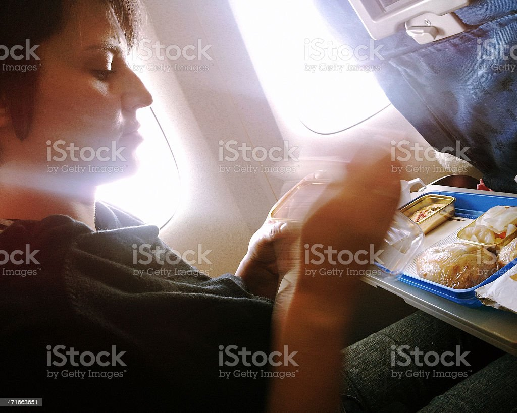 Young woman eats lunch in travel aboard of international flight royalty-free stock photo