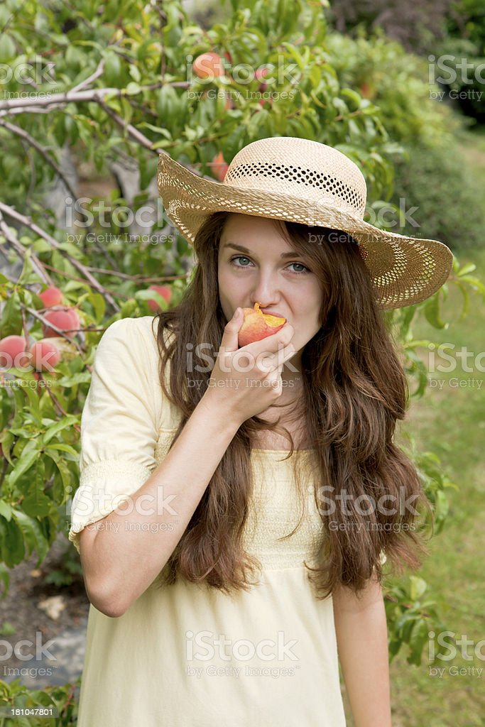 Young woman eats peach royalty-free stock photo