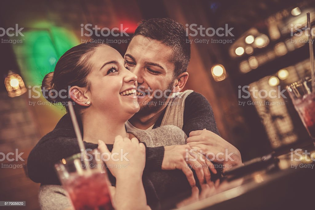Young woman embracing her boyfriend in a bar stock photo