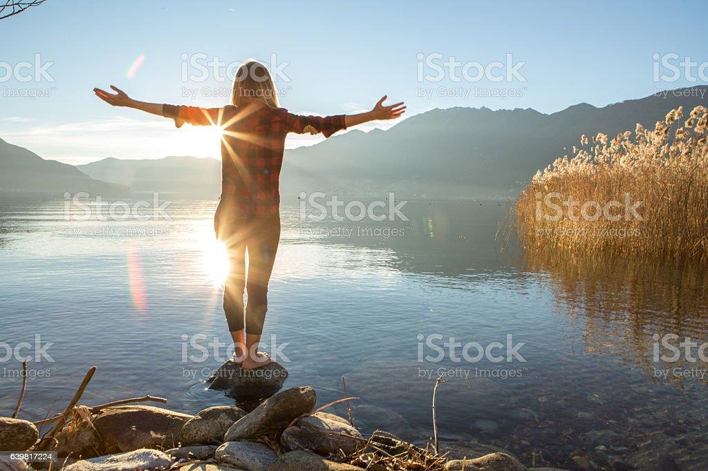 Young woman embracing nature, mountain lake stock photo