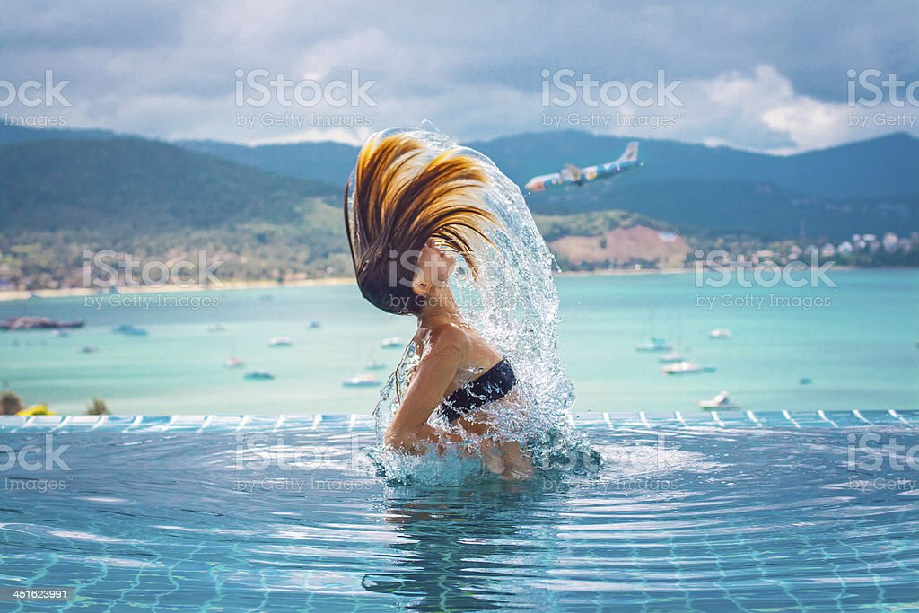 Young woman emerges from the water stock photo