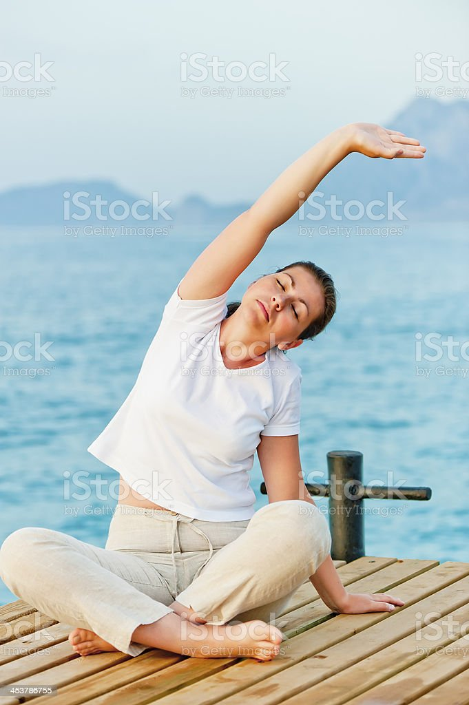 young woman engaged in Pilates by the Sea royalty-free stock photo
