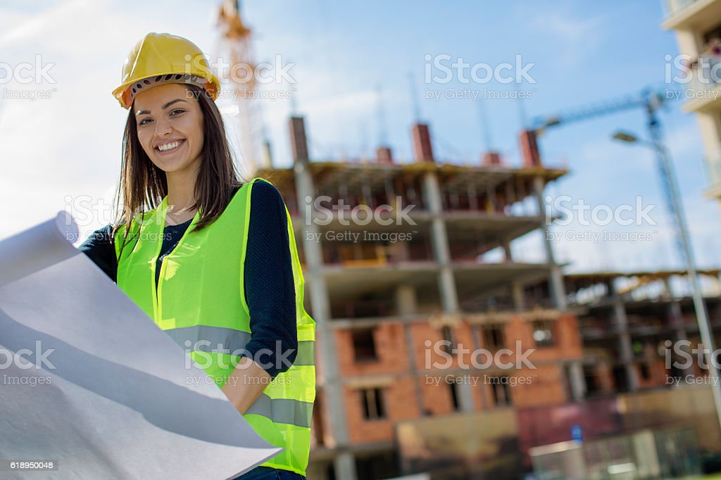 Young woman engineer looking at blueprints stock photo