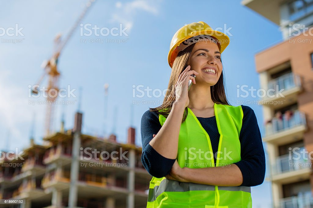 Young woman engineer talking on her cell stock photo
