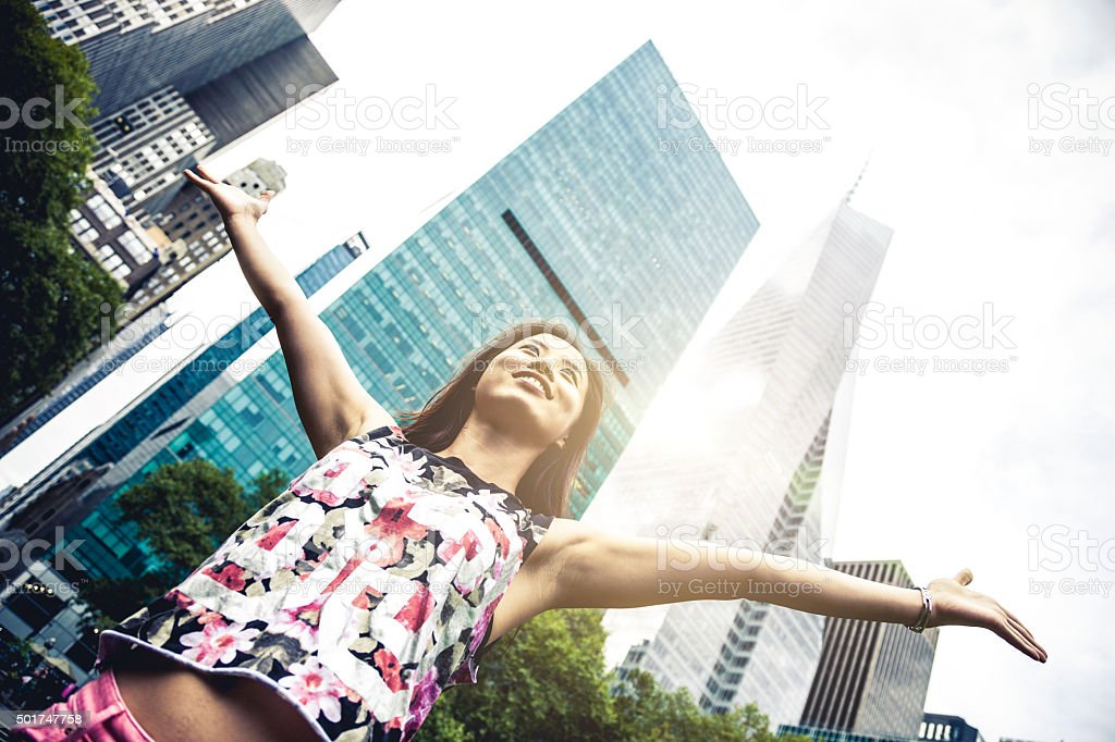 Young woman enjoy freedom in the city park stock photo