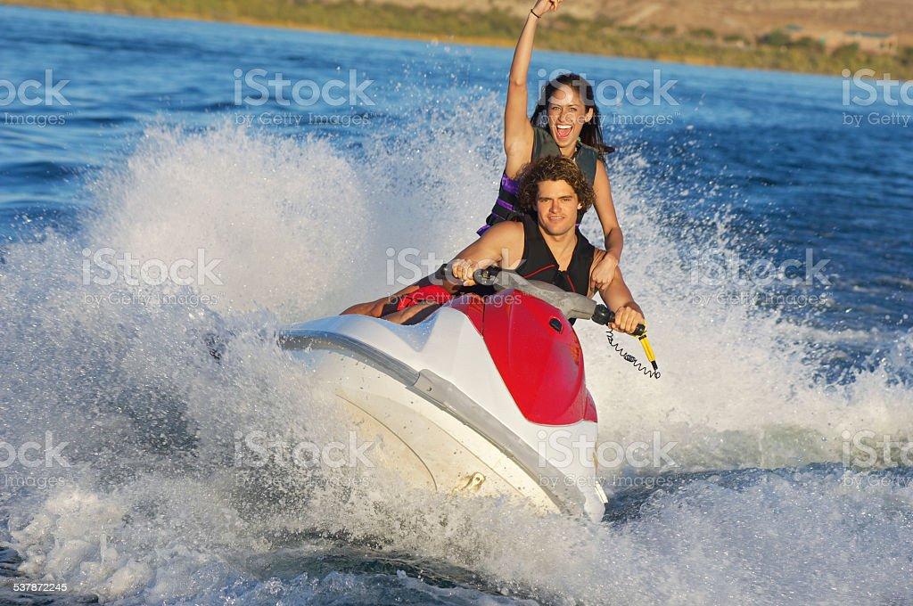 young woman enjoying a ride of jetski at lake stock photo