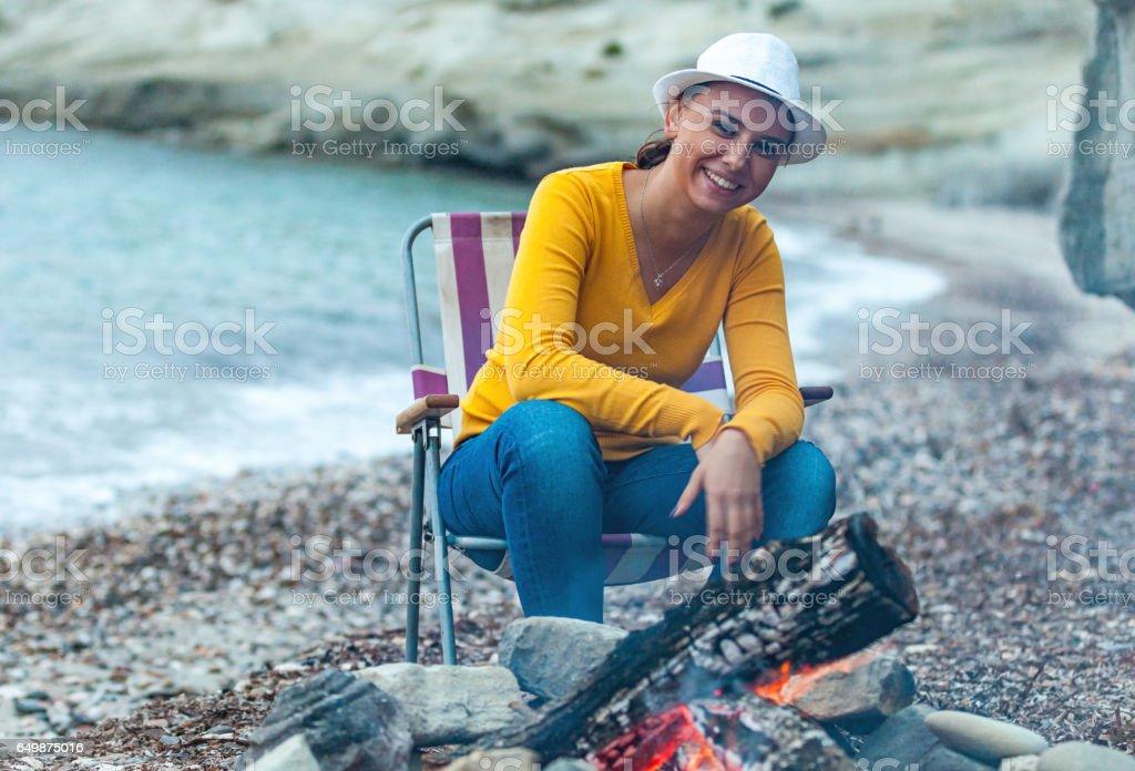 Young woman enjoying bonfire on beach stock photo