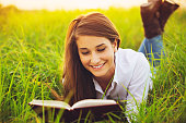 Young Woman Enjoying Book Reading Outdoors