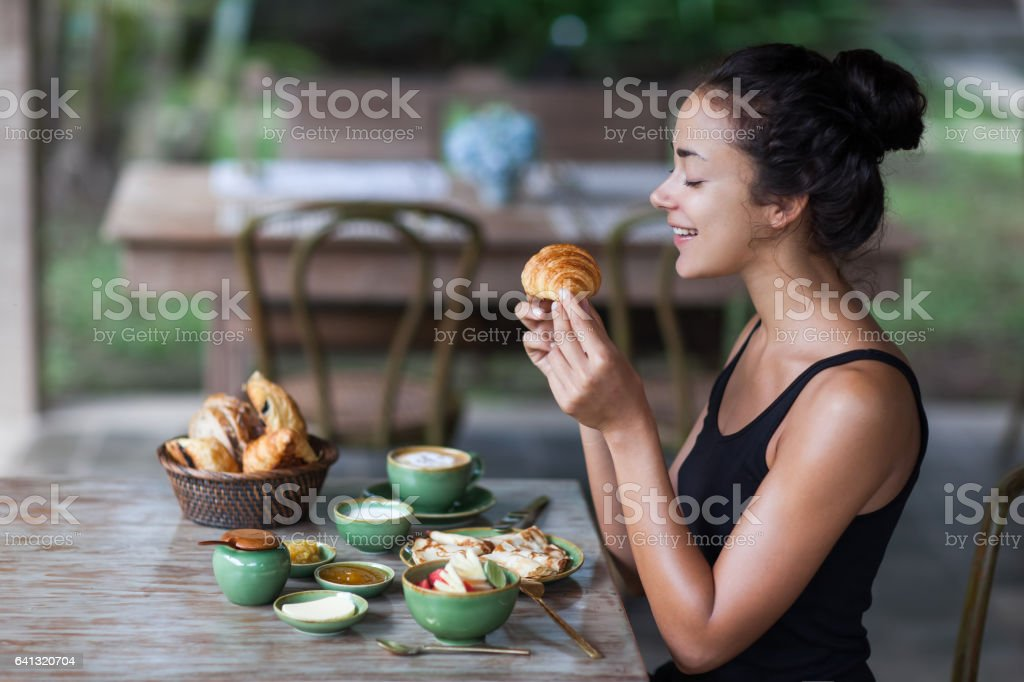 Young woman enjoying breakfast and holding croissant in hand. Morning good mood stock photo