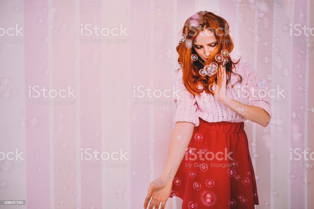 Young Woman Enjoying Bubbles Around Her stock photo