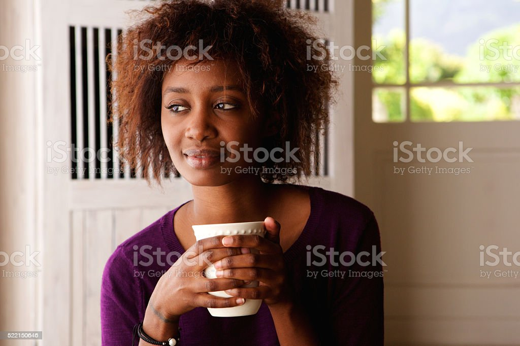 Young woman enjoying cup of coffee at home stock photo
