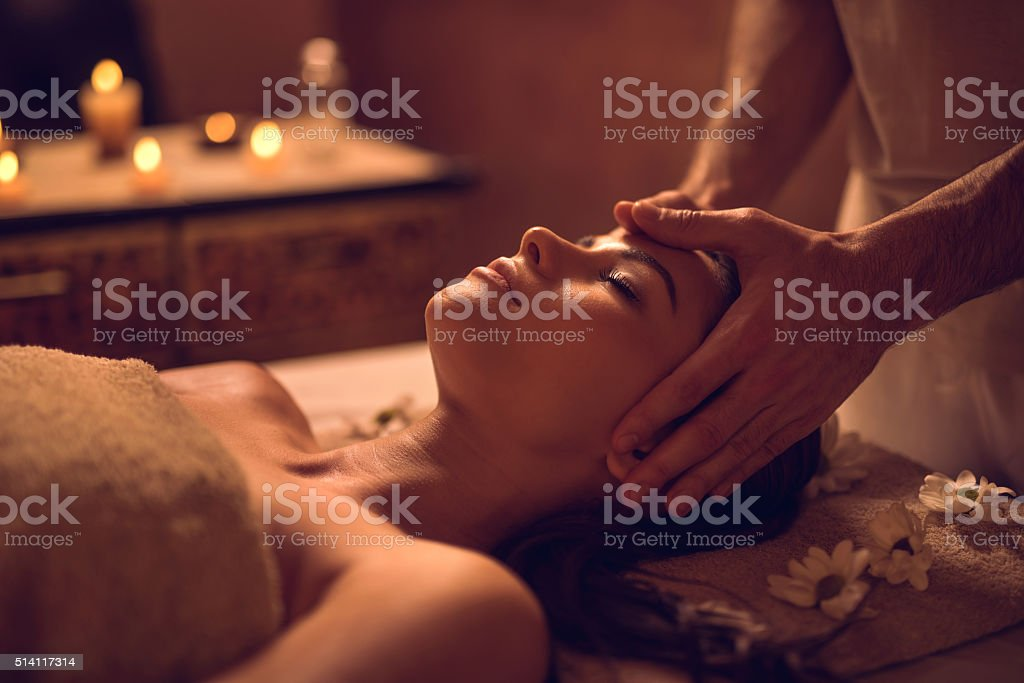 Young woman enjoying during head massage at the spa. stock photo