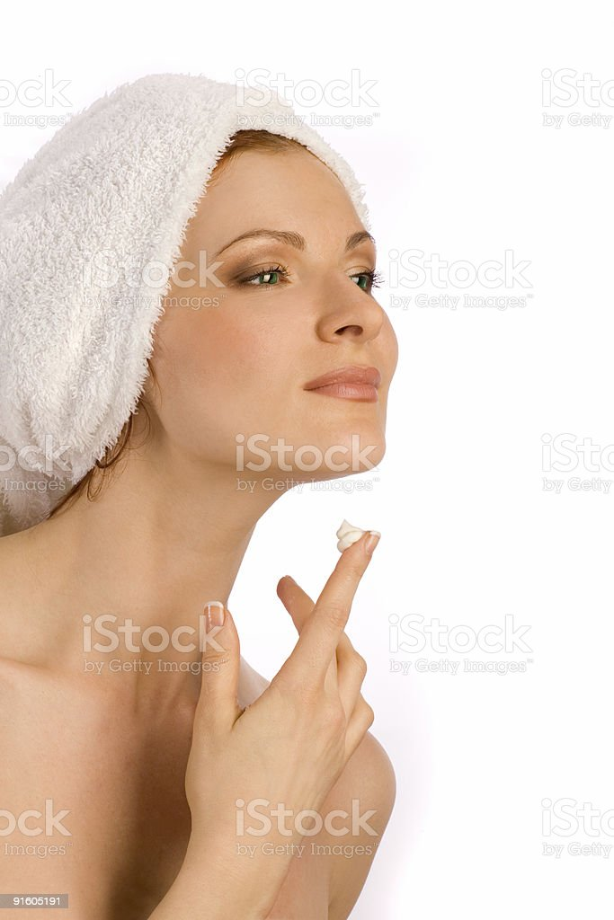 Young woman enjoying her face cream with towel on  head. royalty-free stock photo