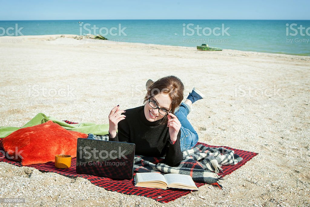 young woman enjoying her working on the beach stock photo