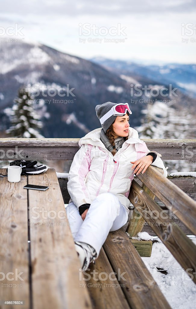 Young woman enjoying in a cafe at ski resort. stock photo