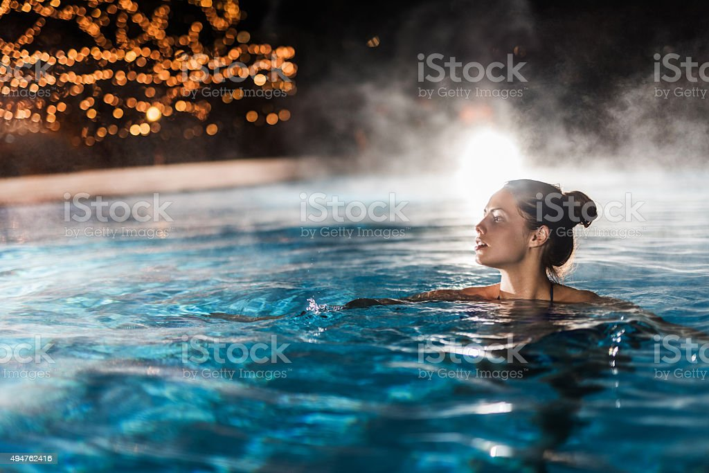 Young woman enjoying in a heated swimming pool at night. stock photo