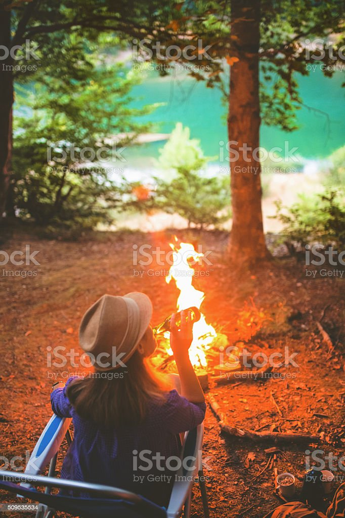 Young woman enjoying in campfire and cold beer stock photo