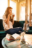 Young woman enjoying in cup of coffee at home.
