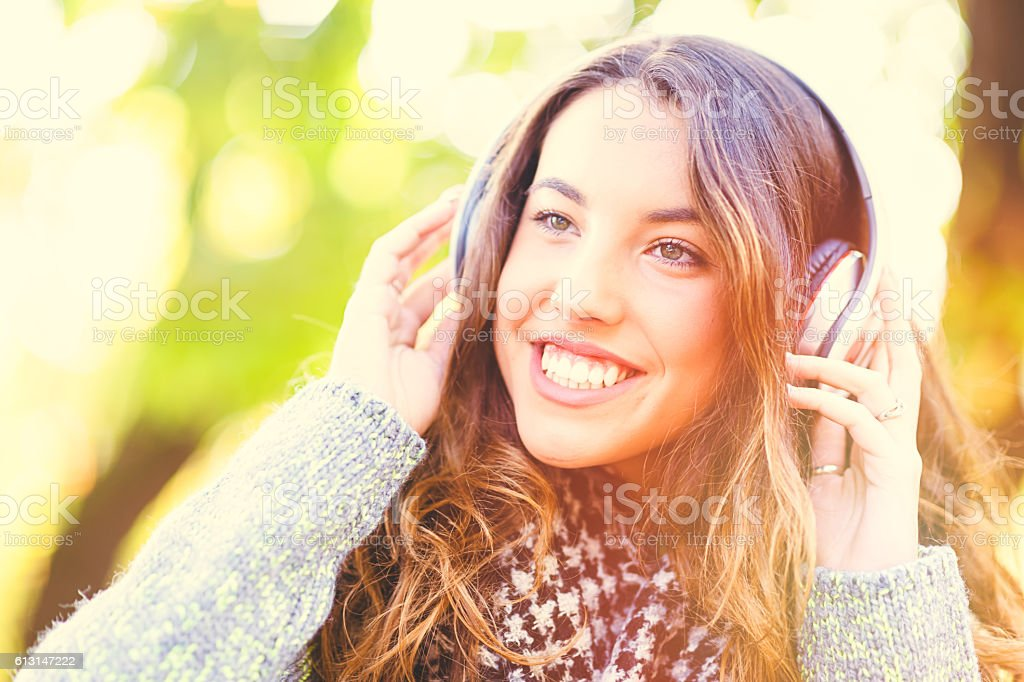 Young woman enjoying music in park stock photo