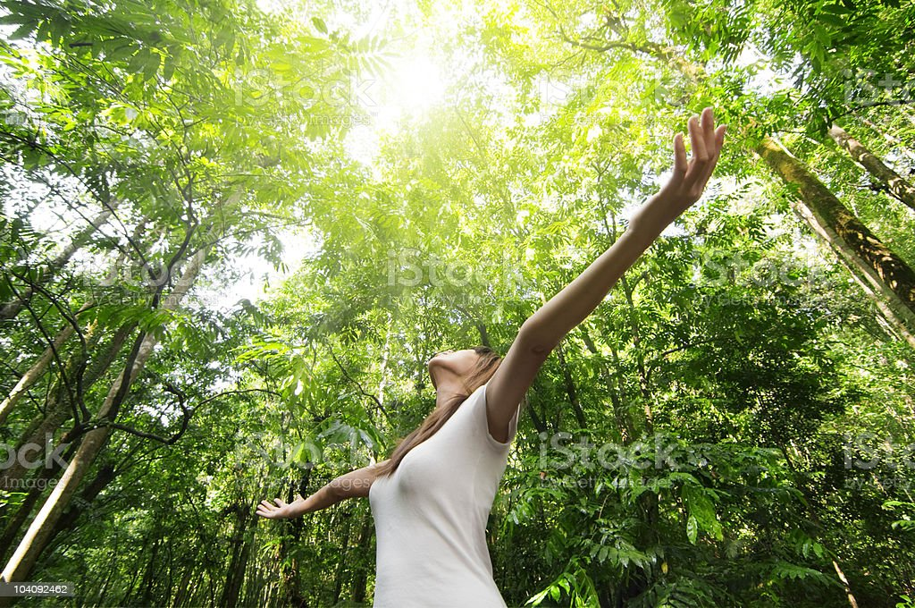 Young woman enjoying nature in green forest stock photo