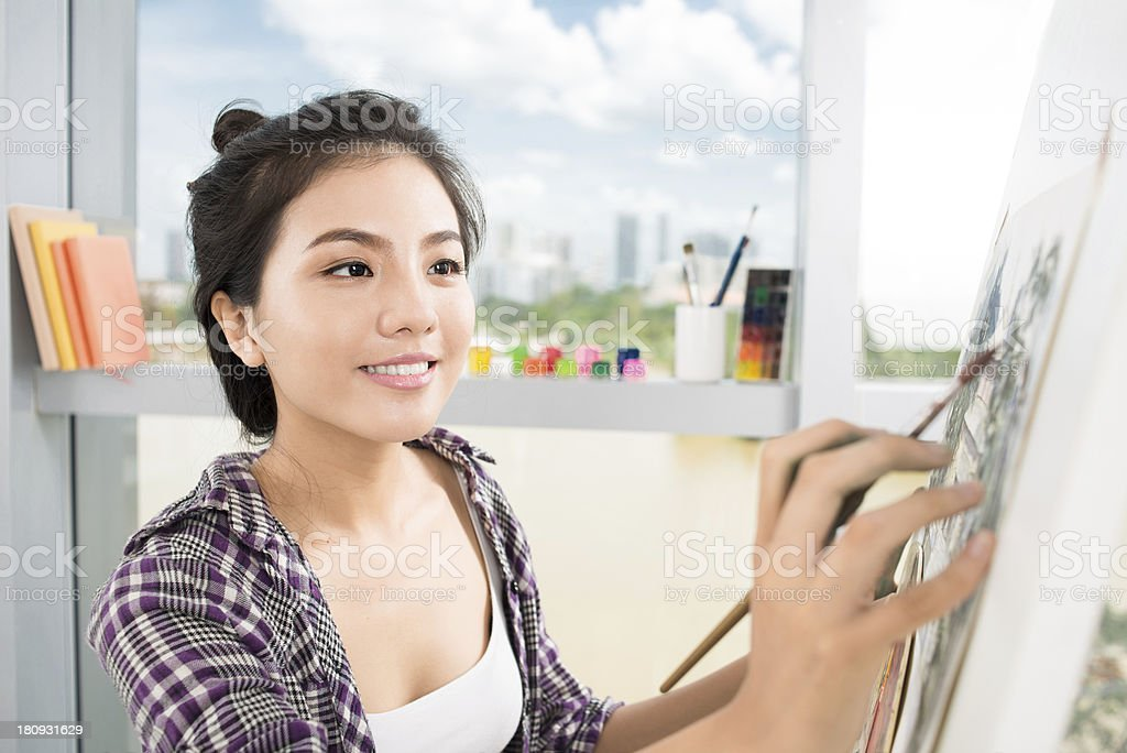 Young woman enjoying painting as a hobby royalty-free stock photo