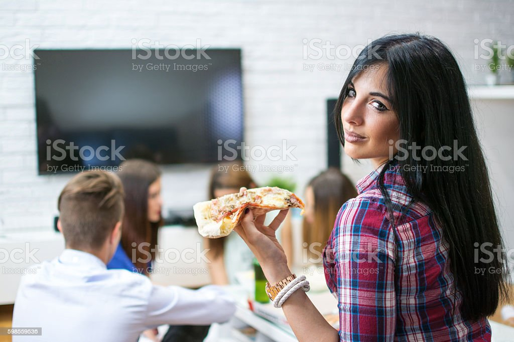 Young woman enjoying slice of pizza  with her friends. stock photo