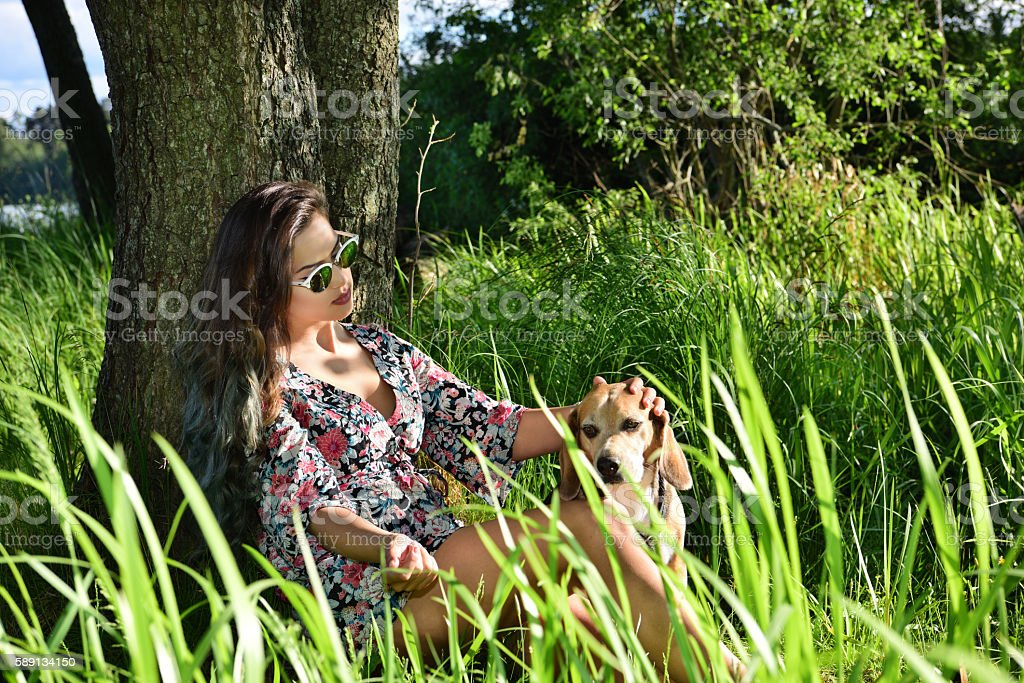 Young woman enjoying Swedish summer with beagle dog in woods stock photo
