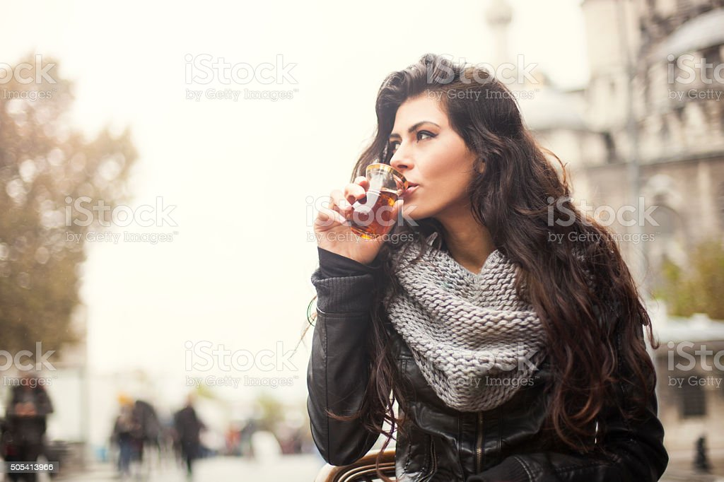 Young Woman Enjoying Turkish Tea Outdoors stock photo
