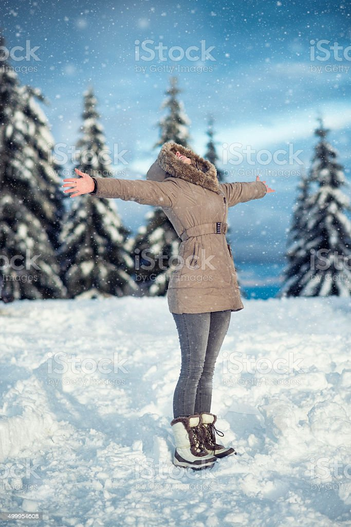 Young Woman Enjoying Winter with Raised Arms While Snowing stock photo