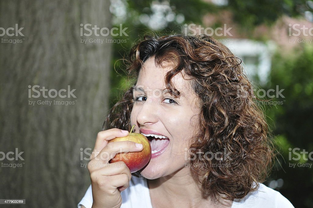 Young woman enjoys an apple stock photo