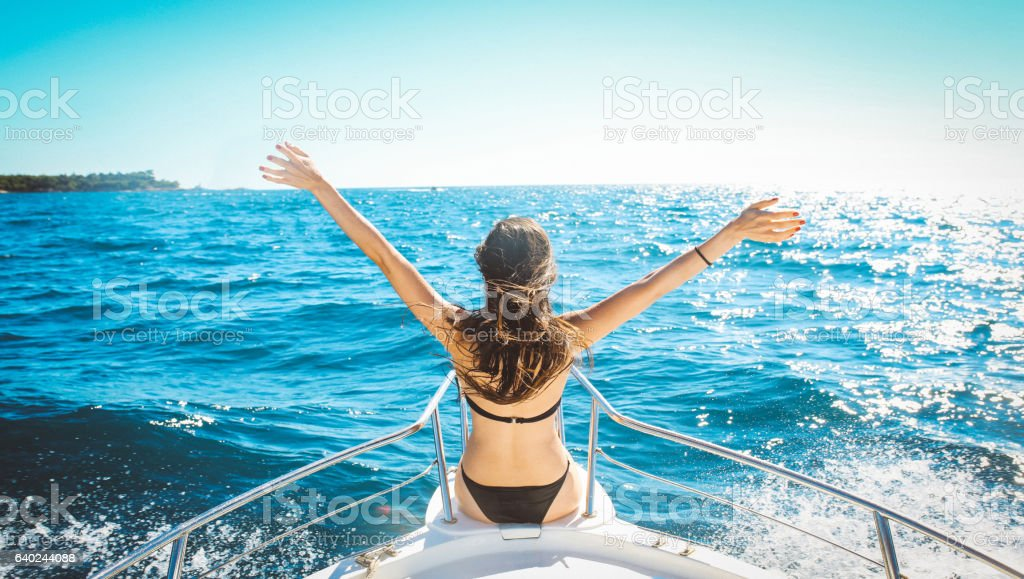 Young woman enjoys boat ride on the seaside stock photo