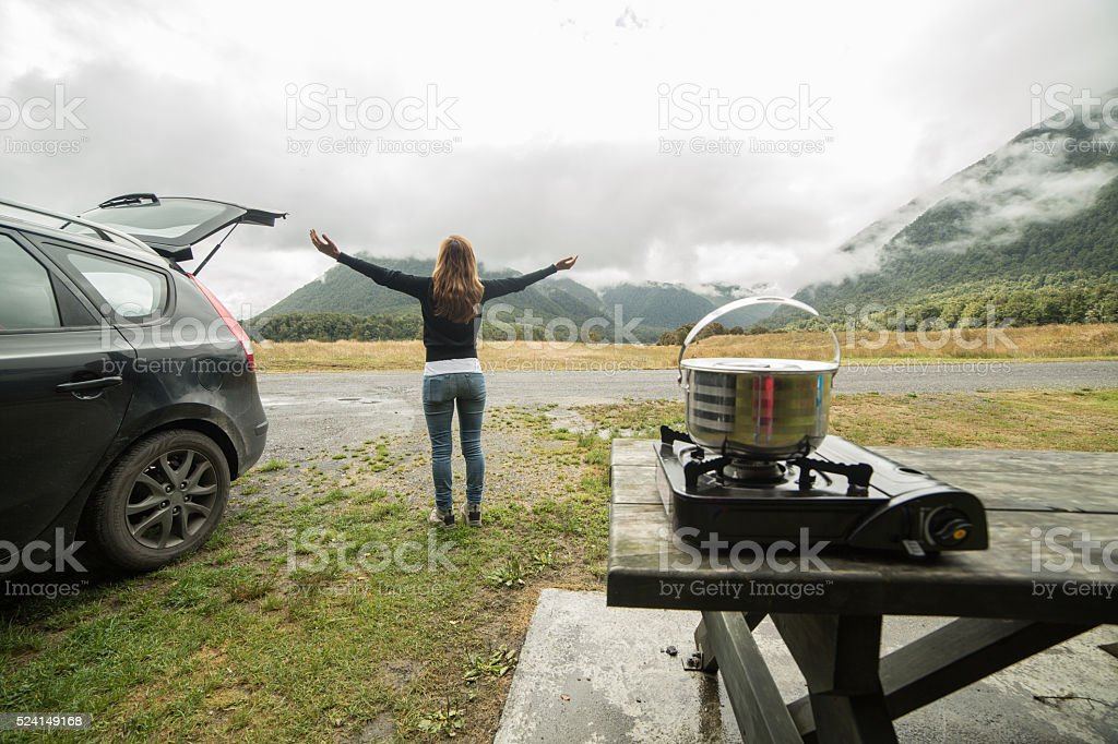 Young woman enjoys camping in New Zealand, arms outstreched stock photo