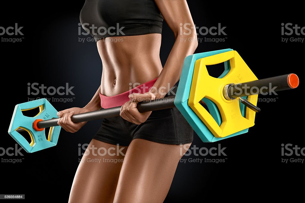 Young woman exercises with barbell isolated over black backgroun stock photo