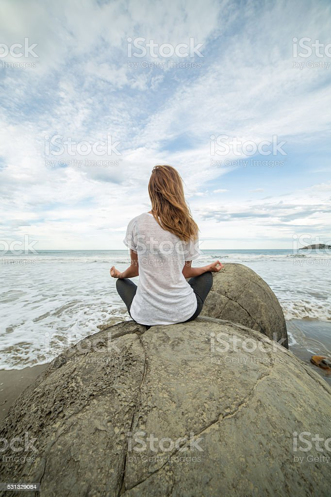 Young woman exercises yoga on spheric boulder by the sea stock photo