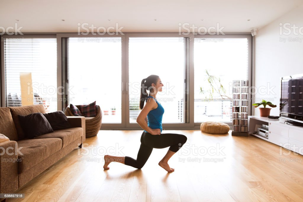 Young woman exercising at home, stretching legs. stock photo