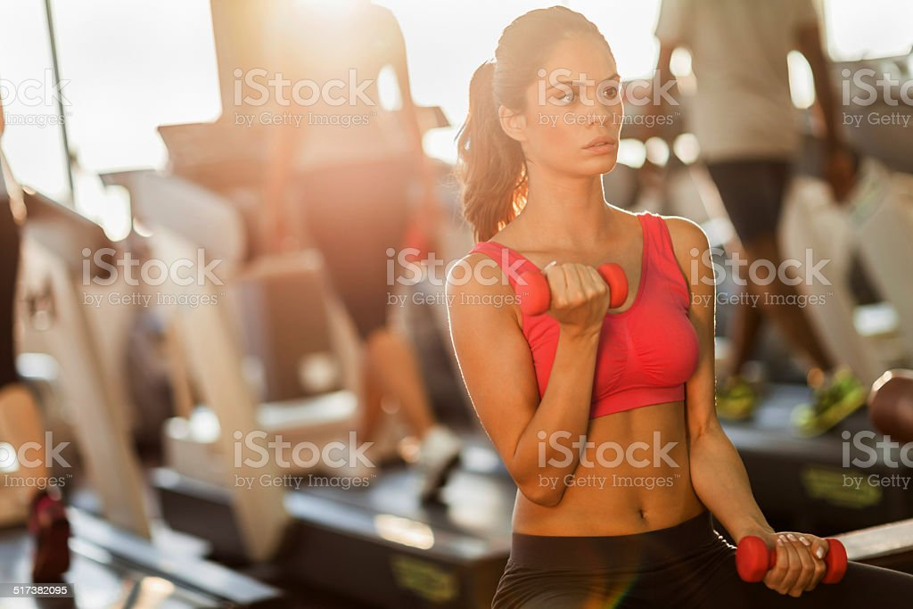 Young woman exercising in gym stock photo