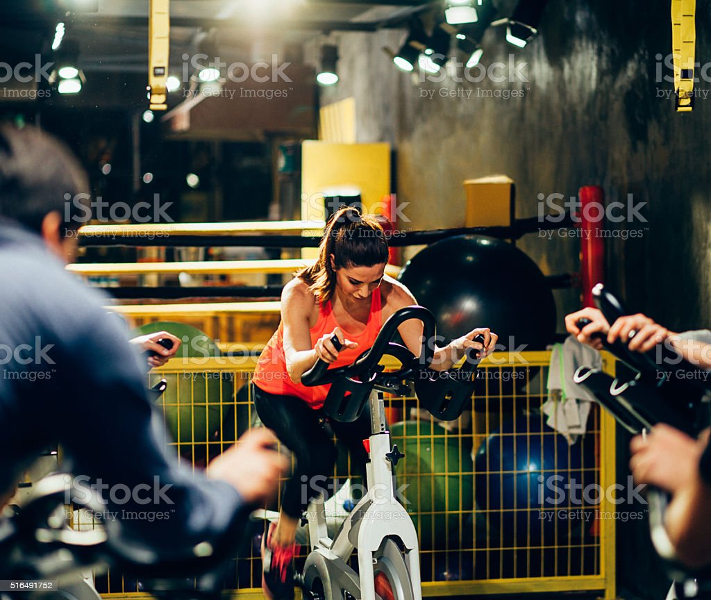 Young woman spinning in the fitness gym stock photo