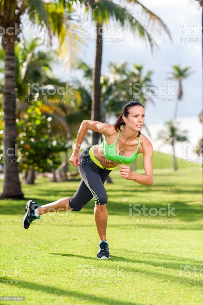 Young woman exercising in tropical park stock photo