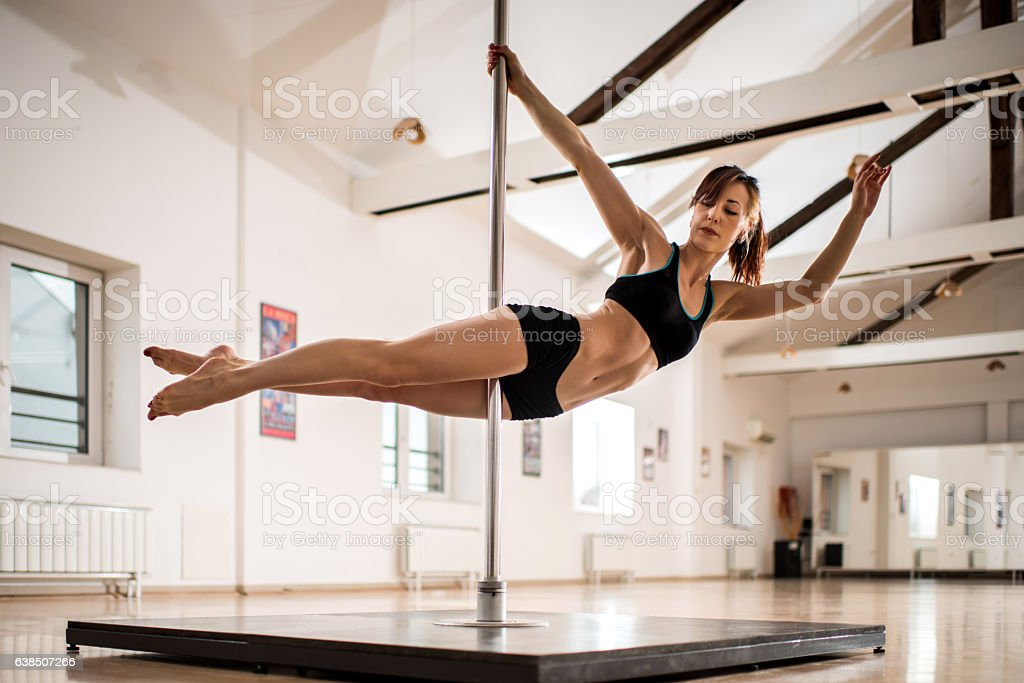 Young woman exercising modern dancing on a pole. stock photo
