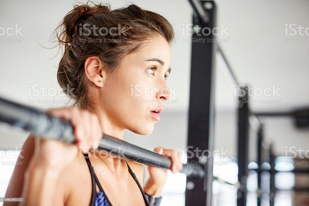 Young woman exercising on pull-up bar in gym stock photo