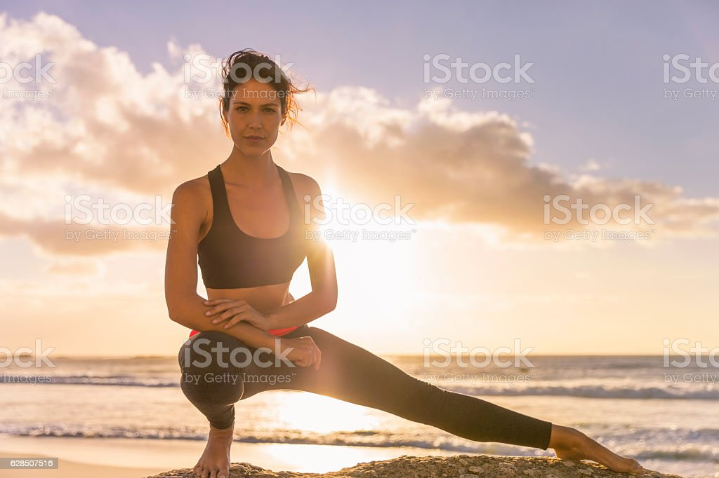 Young woman exercising on shore during sunset stock photo