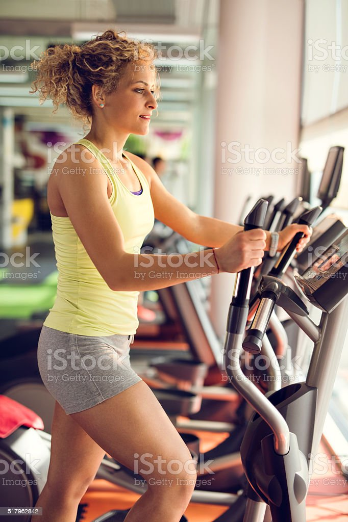 Young woman exercising on stair climbing machine in a gym. stock photo