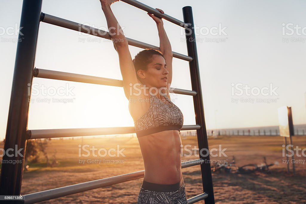 Young woman exercising on wall bars outdoors stock photo